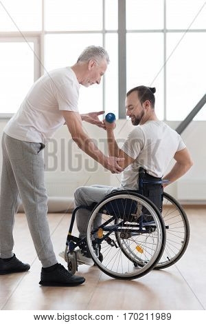 Enjoying my training. Smiling muscular young disabled man holding the dumbbell and having the lesson with the orthopedist in the gym while doing the morning gymnastics and expressing positivity