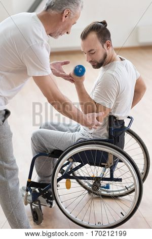 Concentrated on my training. Charismatic muscular young disabled man holding the dumbbell and having the lesson with the orthopedist in the gym while doing gymnastics and expressing positivity