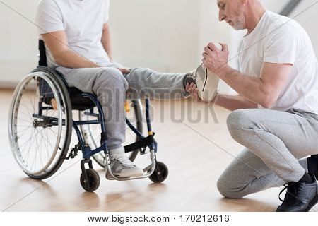 Caring about my patient. Proficient muscular aged orthopedist helping the disabled man and providing a rehabilitation session while expressing concentration and holding the leg of the patient