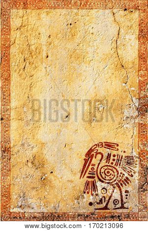 Background with grunge stucco wall texture of yellow color and American Indian traditional patterns with heron