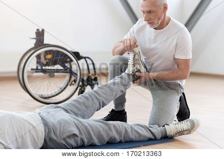 Full of concern. Involved skilled powerful physical therapist helping the invalid and providing a rehabilitation session while expressing concentration and holding the leg of the patient