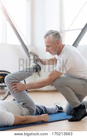 Stretching before exercising. Concentrated skilled athletic orthopedist stretching the invalid and providing a rehabilitation session while expressing concentration and holding the leg of the patient