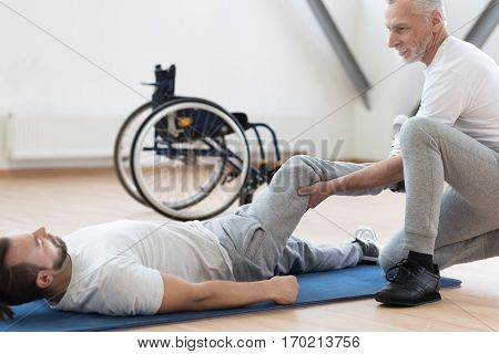 Stretching and exercising. Proficient skilled athletic coach stretching the handicapped and providing a rehabilitation session while expressing concentration and holding the leg of the patient