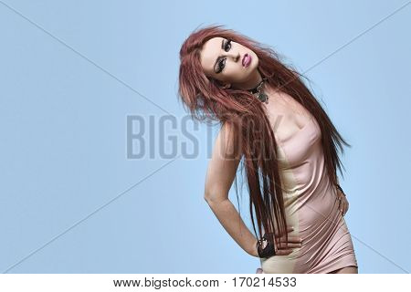 Portrait of funky young woman posing over blue background