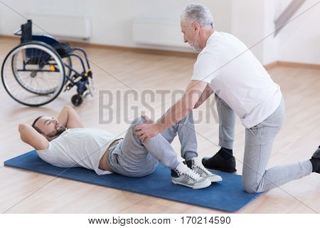 Improving the health. Helpful strong aged general practitioner stretching the handicapped and helping while holding legs of the patient