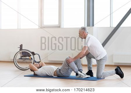 Helping people in need. Helpful athletic aged general practitioner stretching the handicapped and helping him while holding legs of the patient