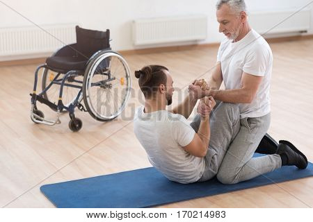Developing the willpower. Positive athletic muscular orthopedist stretching the handicapped and assisting him while holding arms of the patient