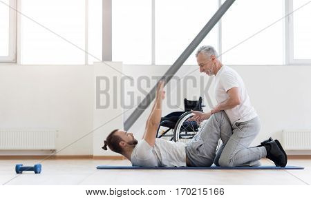 Exercises for disabled in motion. Positive athletic aged orthopedist stretching the disabled and assisting while holding legs of the patient and counting