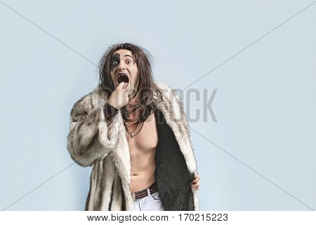 Portrait of young man in fur coat with finger in mouth standing against light blue background
