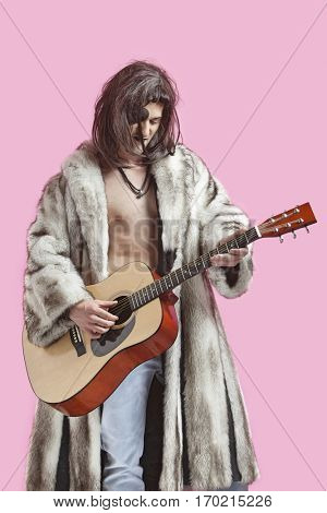 Young man in fur coat playing guitar against pink background