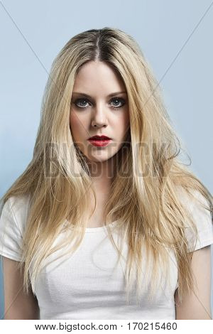 Portrait of attractive young blond woman with red lips against light blue background