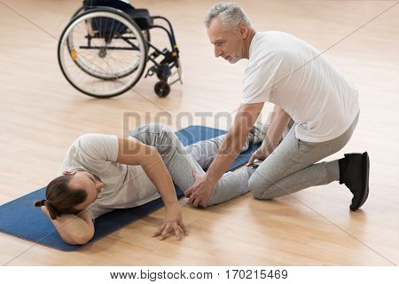 Stretching the disabled patient. Smiling helpful masterful physical therapist stretching the disabled man and assisting while holding leg of the patient and expressing positivity