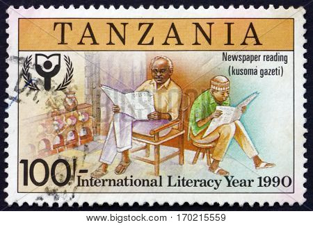 TANZANIA - CIRCA 1991: a stamp printed in Tanzania dedicated to International literacy year reading newspapers circa 1991