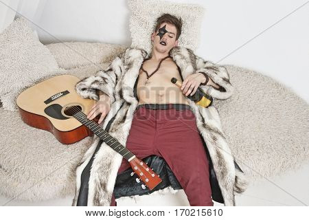 Drunk young man with guitar sleeping on sofa