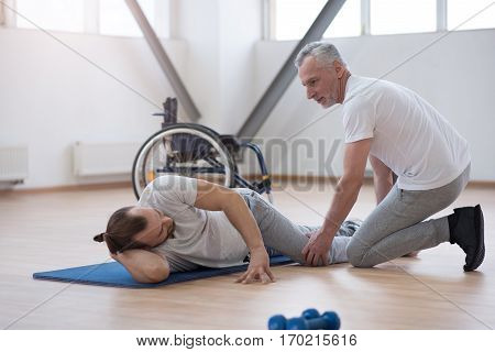 Enjoying helping people. Cheerful helpful skilled physical therapist stretching the disabled man and assisting while holding leg of the patient and expressing joyfulness