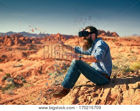 cool bearded guy wearing vr goggles in nevada desert with digital effect