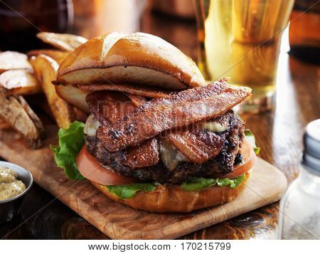 bacon burger with pretzel bun and beer