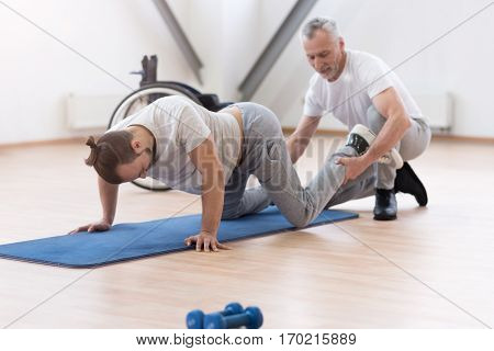 Helping my disabled friend. Positive friendly bearded orthopedist stretching the handicapped and assisting while holding legs of the patient and expressing concentration