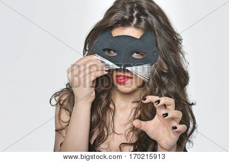 Portrait of sensuous young woman wearing cat mask while biting lip over gray background