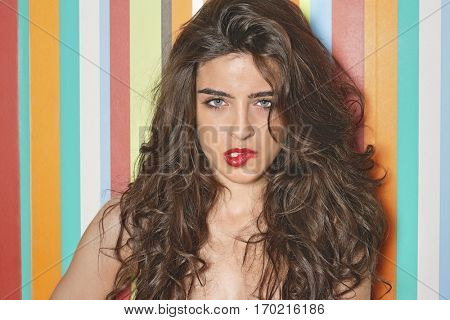 Portrait of a sensuous young woman biting lips against colorful striped background