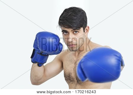 Portrait of an Indian shirtless man wearing blue boxing gloves against gray background
