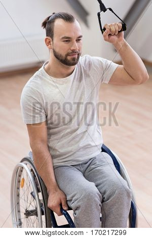Enjoying active way of life. Delighted muscular strong disabled sitting in the wheelchair in the gym and expressing happiness while exercising and stretching the rubber cable