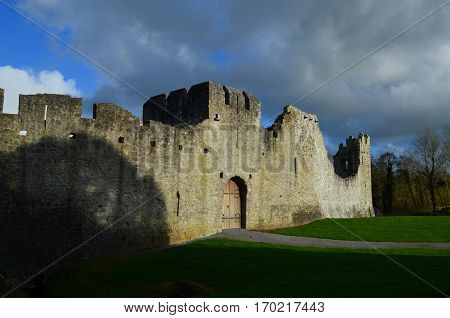 Dark storm clouds over the ruins of Desmond Castle in Ireland.