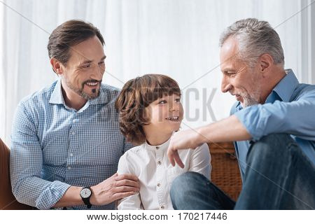 Pleasant interaction. Handsome delighted pleasant grandfather looking at his grandson and speaking with him while spending time with his family members