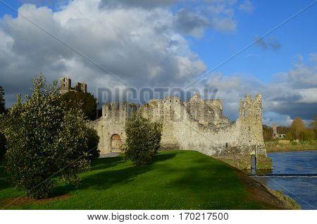 Sun shining on Desmond Castle ruins wiith River Maigue.