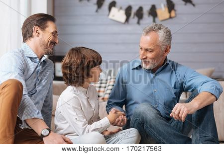 Family greetings. Cheerful positive elderly man shaking his grandsons hand and smiling while greeting him