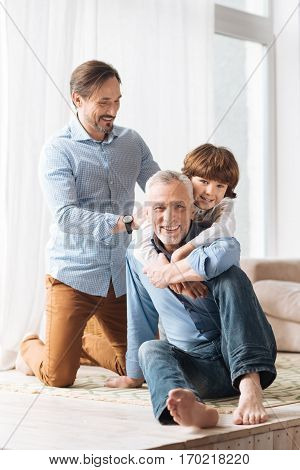 Care and love. Happy cute young boy standing behind his grandfather and hugging him while expressing his love for him