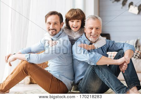 Expressing love. Cute delighted positive child sanding between his father and grandfather and laughing while hugging them