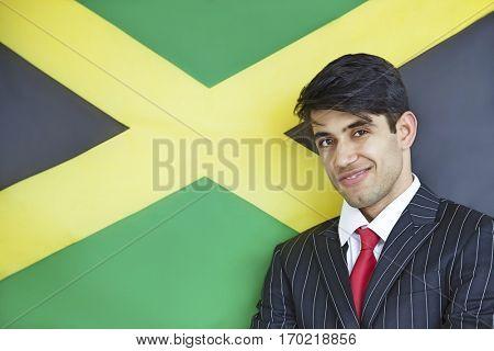 Portrait of a young confident businessman against Jamaican flag