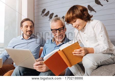 Reading a story. Happy young cute boy holding a book and showing it to his grandfather while reading a story