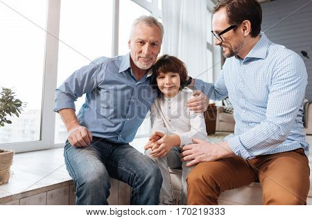 Care and support. Delighted happy nice family sitting together and smiling while being in the great mood