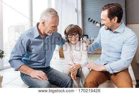 Bad eyesight. Cute pleasant young child sitting between his father and grandfather and wearing glasses while having problems with the eyesight