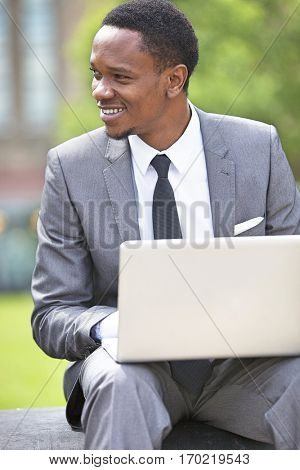Three-quarter portrait of African American Businessman working on a laptop outdoors