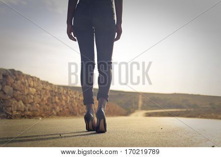 Black girl walking in high heels on endless coutry road