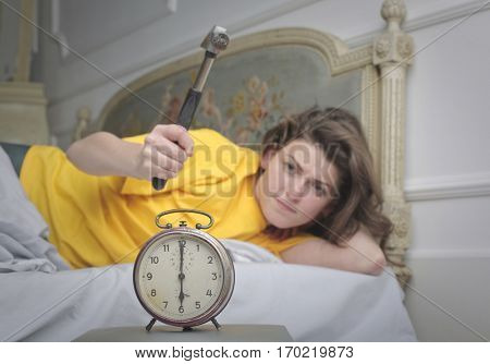 Beuatiful girl trying to kill the alarm with a hamer