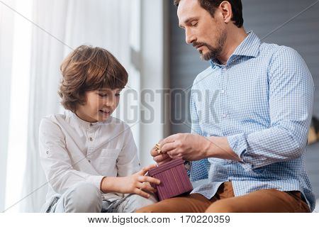 Preparing a present. Handsome nice delighted man holding a gift box and tying a bow while preparing a present with his son