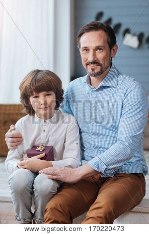 Time for presents. Cute young delighted boy sitting near his father and being hugged by him while holding a present