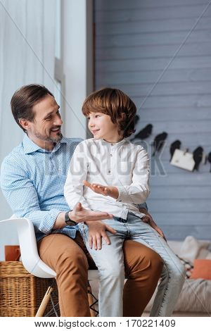 I love my father. Delighted nice young child sitting on his fathers knees and looking at him while being in a great mood