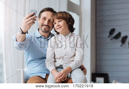 Moment to remember. Nice happy delighted man having a son on his laps and holding a smartphone while taking a selfie poster