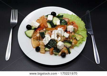 Greek salad on a white plate with fork and knife on a black background. Can be used as a photo for restaurant menus, bistro. European, Mediterranean cuisine.