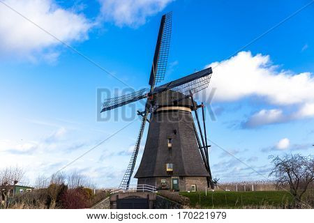 Traditional dutch windmill near the canal. Netherlands. Old windmill stands on the banks of the canal, and water pumps.