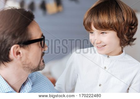 Positive mood. Cheerful young nice boy looking at his father and smiling while spending time with him