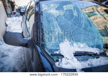 Image of the broken windshield of a car after a piece of ice has fallen from the roof of a house.
