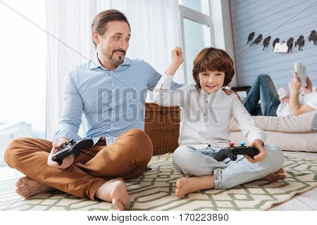 My victory. Positive young delighted boy sitting cross legged on the floor and holding his hand up while playing video games with his father
