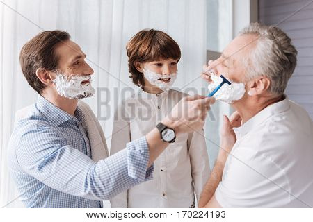 Do you need help. Nice handsome positive man holding a razor and looking at his father while helping him to shave