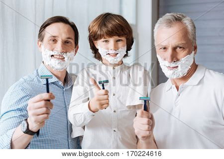 Preparing to shave. Positive nice happy family looking at you and holding razors while preparing to shave